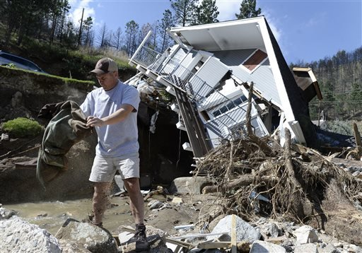 In this Sept. 19, 2013 photo, Sean McCroskey pulls his wife Meg's jacket out of the debris in the river in front of their destroyed home on Gold Run Road in Boulder County, Colo.
