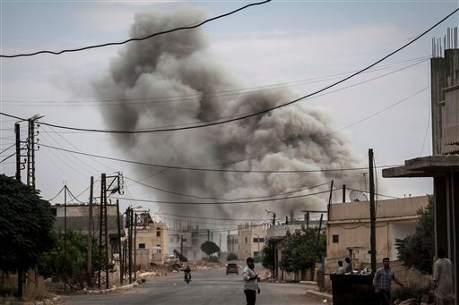 In this Sunday, Sept. 22, 2013 photo, smoke rises due to an air strike that hit a village turned into a battlefield between Free Syrian Army fighters and government forces in Idlib province, northern, Syria. (AP Photo)