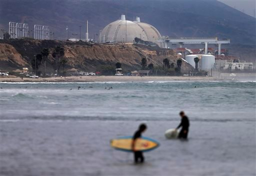 In this June 7, 2013 file photo surfers pass in front of the San Onofre nuclear power plant.