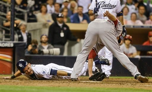 San Diego Padres' Reymond Fuentes gets a hand on home plate while scoring from third on a pass ball to tie the game against the Arizona Diamondbacks in the eighth inning of a baseball game Tuesday, Sept. 24, 2013, in San Diego.(AP Photo/Lenny Ignelzi)
