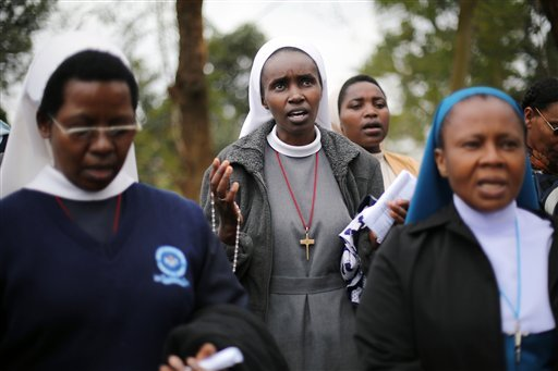 Catholic nuns pray near the Westgate Mall in Nairobi, Kenya Wednesday, Sept. 25 2013. Gunshots rang out from the upscale mall Wednesday morning, the day after the president declared an end to a four-day siege by Islamic militants. (AP Photo/ Jerome Delay)
