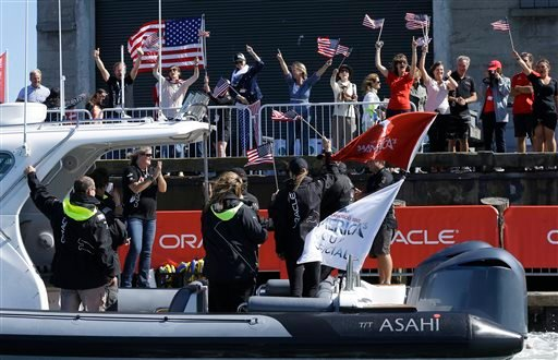 Fans cheer as a boat carrying Oracle CEO Larry Ellison passes a pier after Oracle Team USA defeated Emirates Team New Zealand in the 18th race of the America's Cup sailing event Tuesday, Sept. 24, 2013, in San Francisco.
