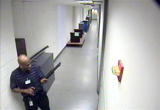 This image from video provided by the FBI, shows Aaron Alexis moves through the hallways of Building #197 at the Washington Navy Yard on Monday, Sept. 16, 2013, in Washington, carrying a Remington 870 shotgun. (AP)