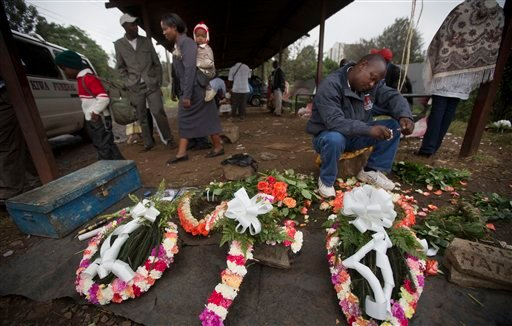 A street-seller makes floral wreaths outside the mortuary in Nairobi, Kenya Wednesday, Sept. 25, 2013. (AP)