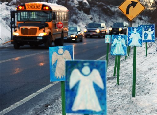 In this Thursday, Jan. 3, 2013 file photo, a bus traveling from Newtown, Conn., to Monroe stops near 26 angel signs posted along the roadside in Monroe, Conn. (AP Photo/Jessica Hill, File)