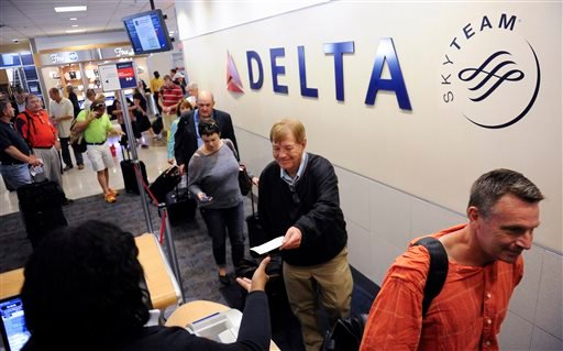 In this Friday, Sept. 27, 2013, photo, Delta Air Lines passengers, who have purchased an upgrade to board their flight early, take advantage of priority boarding as they make their way to their flight at Hartsfield-Jackson Atlanta International Airport.