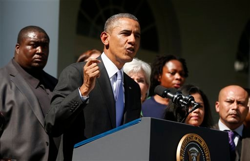 President Barack Obama stands with people who support the Affordable Care Act, his signature health care law, as he speaks in the Rose Garden of the White House in Washington, Tuesday, Oct. 1, 2013.