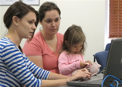 Debora Costa right, tries to sign up for insurance coverage for her two children, including 2-year-old Victoria, Wednesday, Oct. 2, 2013. (AP Photo/David Mercer)
