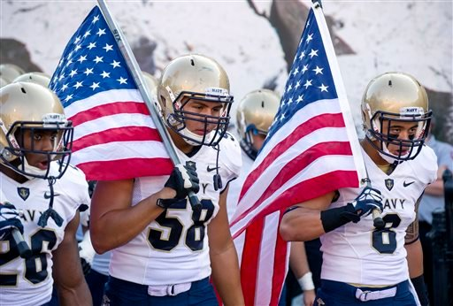 FILE - In this Sept. 7, 2013, file photo, from left, Navy's Marcus Thomas (26), Evan Palelei (58) and Wave Ryder (8) head onto the field at the start of an NCAA college football game against Indiana in Bloomington, Ind. (AP)