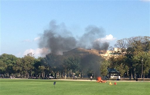 In this photo provided by Katy Scheflen, people run to a man who set himself on fire on the National Mall in Washington, Friday, Oct. 4, 2013. The reason for the self-immolation was not immediately clear and the man's identity was not disclosed.
