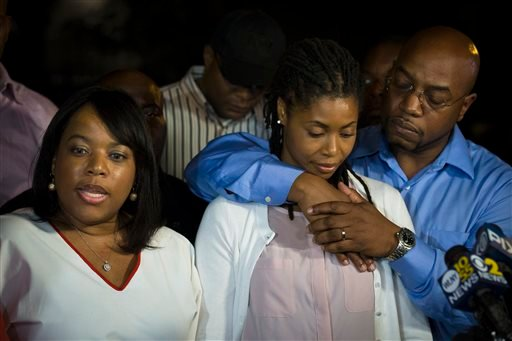 Amy Carey-Jones, center, sister of Mariam Carey, reacts as her sister Valarie, left, speaks to the media outside her home in the Bedford-Stuyvesant neighborhood of Brooklyn, Friday, Oct. 4, 2013, in New York.