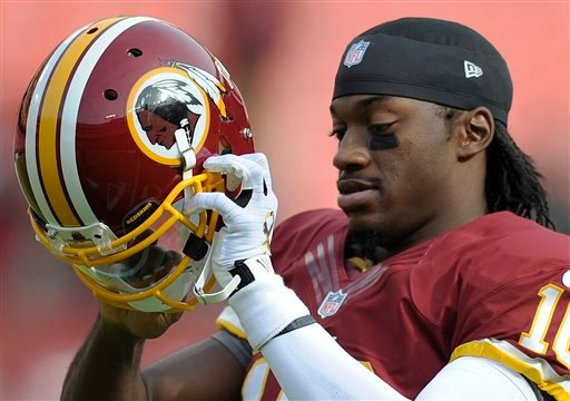 In this Sunday, Nov. 18, 2012 photo, Washington Redskins quarterback Robert Griffin III prepares to put on his helmet before an NFL football game against the Philadelphia Eagles in Landover, Md.