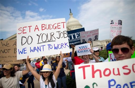 Protestors hold signs during a during an event with the Democratic Progressive Caucus and furloughed federal employees on Capitol Hill in Washington, Friday, Oct. 4, 2013, as the budget battle continued.