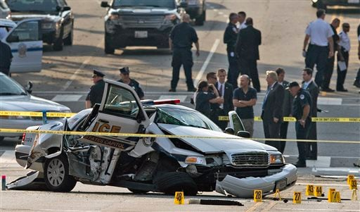 A damaged Capitol Hill police car is surrounded by crime scene tape after a car chase and shooting in Washington, Thursday, Oct. 3, 2013.
