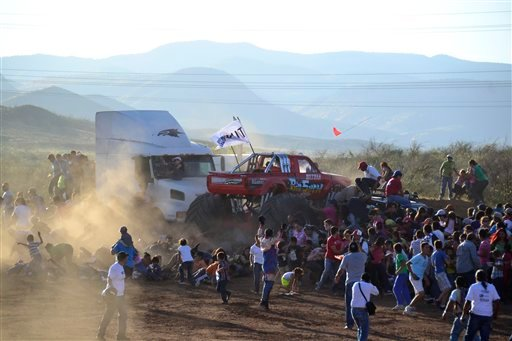 People run as an out of control monster truck plows through a crowd of spectators at a Mexican air show in the city of Chihuahua, Mexico, Saturday Oct. 5, 2013. According to authorities, at least 8 people were killed and 80 were injured.