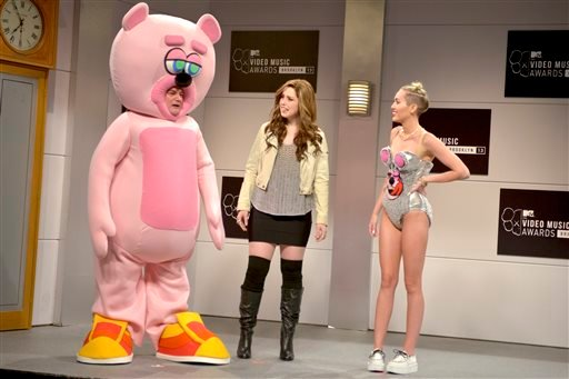 """This Oct. 5, 2013 photo released by NBC shows, from left, Bobby Moynihan, Vanessa Bayer and guest host Miley Cyrus in a scene from the late-night comedy series """"Saturday Night Live,"""" in New York. (AP Photo/NBC, Dana Edelson)"""
