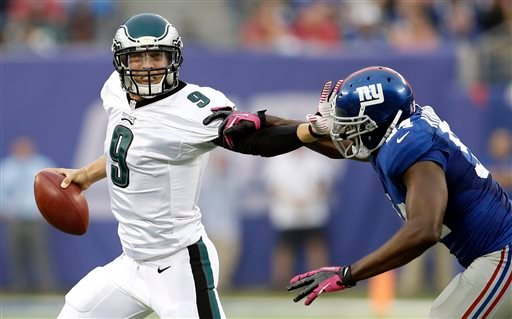 Philadelphia Eagles' Nick Foles (9) stiff-arms New York Giants' Mathias Kiwanuka (94) during the second half of an NFL football game on Sunday, Oct. 6, 2013, in East Rutherford, N.J. (AP Photo/Kathy Willens)
