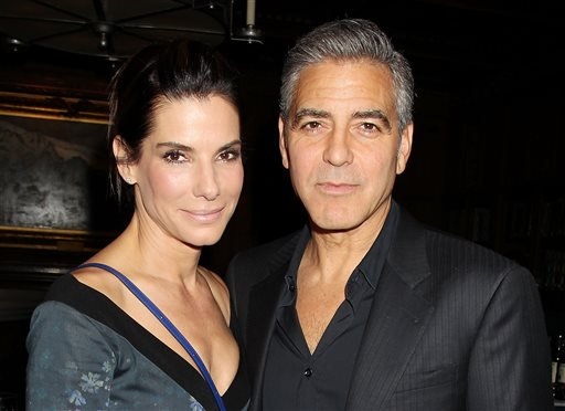 """This image released by Starpix shows Sandra Bullock, left, and George Clooney at luncheon honoring the film """"Gravity,"""" and hosted by The Peggy Siegal Company and Warner Brothers Pictures at The Explorers Club, Wednesday, Oct. 2, 2013 in New York."""