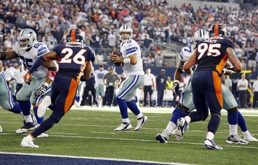 Dallas Cowboys quarterback Tony Romo, center, looks to pass against the Denver Broncos during the third quarter of an NFL football game Sunday, Oct. 6, 2013, in Arlington, Texas. (AP Photo/Sharon Ellman)