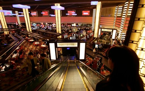 In this file photo taken Wednesday, Nov. 14, 2007, guests descend an escalator to the main casino floor of the Planet Hollywood Resort & Casino in Las Vegas.