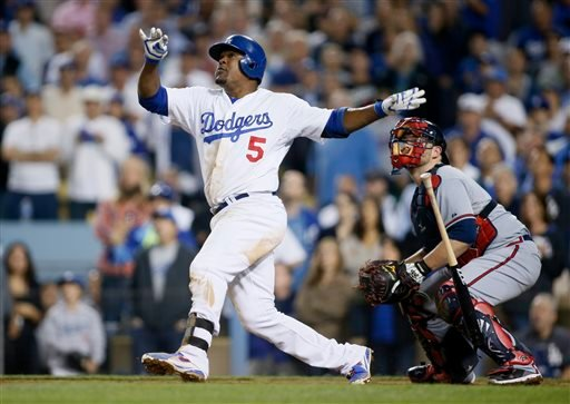 Los Angeles Dodgers third baseman Juan Uribe drops his bat and watches his two-run home run in front of Atlanta Braves catcher Brian McCann in the eighth inning of Game 4 in the National League baseball division series Monday, Oct. 7, 2013, in Los Angeles