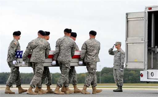 An Army carry team moves a transfer case containing the remains of Pfc. Cody J. Patterson Wednesday, Oct. 9, 2013 at Dover Air Force Base, Del. (AP Photo/Steve Ruark)