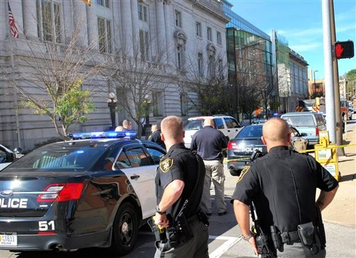 Local law enforcement officers secure an area in front of the Federal Buildng in Wheeling, WV, Wedneday, Oct. 9, 2013, following a shooting outside the courthouse. (AP Photo/The Intelligencer, Scott McCloskey)