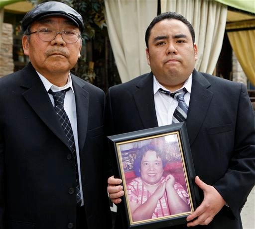 "This Thursday, Feb. 4, 2010 file photo shows Jeffrey Uno, right, and his father, Peter Uno, the son and husband of Noriko Uno, in framed photo, who died in an alleged ""sudden unintended acceleration"" crash in a Toyota Camry in August 2009, in Los Angeles."