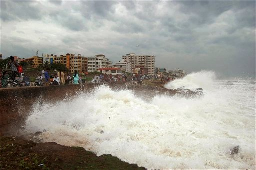 Indian people watch high tide waves as they stand at the Bay of Bengal coast in Vishakhapatnam, India, Saturday, Oct. 12, 2013.