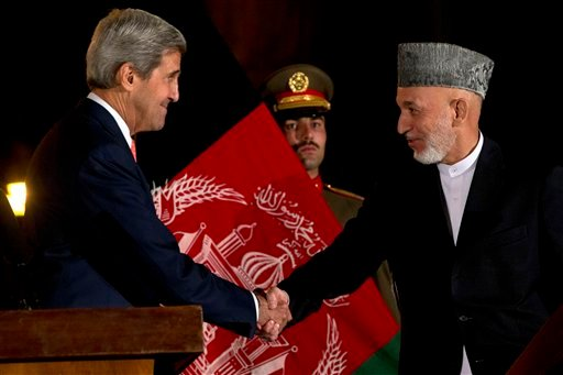 U.S. Secretary of State John Kerry shakes hands with Afghan President Hamid Karzai after they made remarks during a news conference at the Presidential Palace during an unannounced stop in Kabul, Afghanistan, on Saturday, Oct. 12, 2013.
