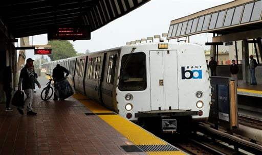 Bay Area Rapid Transit travelers wait to board an arriving train Saturday, Oct. 12, 2013, in Oakland, Calif.