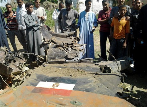Egyptians gather around the remains of a Soviet-made MiG-21 fighter jet belonging to the Egyptian air force that crashed Sunday, while on a training mission near the southern ancient city of Luxor, which officials said killed a villager on the ground.