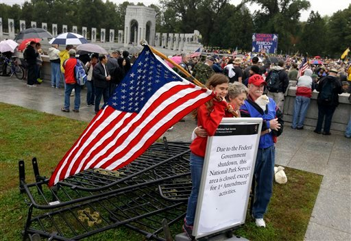 Kaylee Cantrell, left, 13, from Lexington Park, Md., with Sherry Cantrell and Michael Cantrell, both from Crossville, Tenn., pose for a photo in front of a sign and removed barricades at the World War II Memorial in Washington Sunday, Oct. 13, 2013.