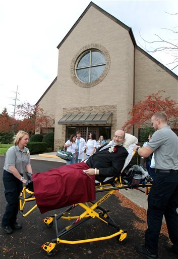 In this Oct. 12, 2013 photo, Scott Nagy is wheeled from First Lutheran Church in Strongsville by paramedics to a spot in the parking lot so he could see his daughter, Sarah Salvatore, and new husband. (AP Photo/The Plain Dealer, John Kuntz)