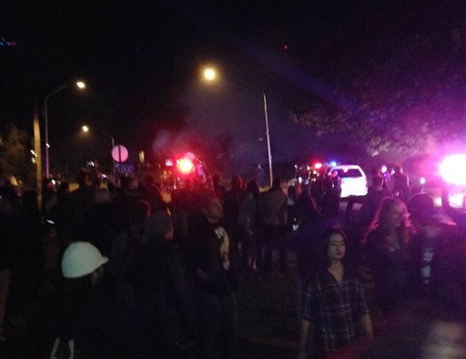 In this photo provided by Lauren Boushey, hundreds of college-age revelers crowd a street late Saturday, Oct. 12, 2013, in Bellingham, Wash., as police try to disperse the crowd.