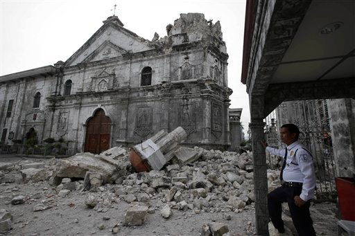 A private guard stands near the damaged Basilica of the Holy Child following a 7.2-magnitude earthquake that hit Cebu city in central Philippines and toppled the bell tower of the Philippines' oldest church Tuesday, Oct. 15, 2013.