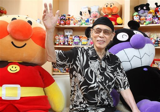 In this Aug. 2011 photo, Takashi Yanase, creator of one of Japan's most beloved cartoon characters, Anpanman, waves accompanied by Anpanman, left, and Baikinman at his Yanase Studio in Tokyo.