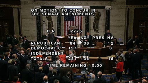 "With partial voting totals on the screen, a woman, just below the House presiding officer, seen between the ""yea"" and ""nay"" wording, is removed from the House chamber. (AP Photo/House TV)"