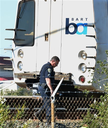 A BART police officer looks along the outside of a BART car that struck and killed two people along Jones Road in Walnut Creek, Calif., on Saturday, Oct. 19, 2013. (AP Photo/The Mercury News, Dan Rosenstrauch)
