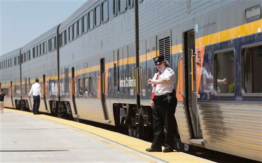 In this photo taken Tuesday, July 16, 2013, an Amtrak conductor checks the time as the passenger train takes on passengers in Hanford, Calif.