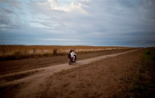 In this May 3, 2013, photo, students ride a motorbike past a field of biotech corn on their way to school in Pozo del Toba, Santiago del Estero province, Argentina.