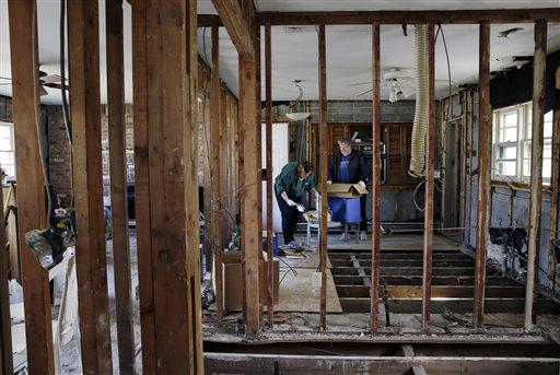 Lee Ann Newland and husband John Lambert, sort through items, inside their Superstorm Sandy damaged home near the Shark River in Neptune, N.J., Sunday, Oct. 13, 2013.