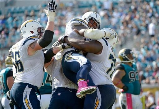 San Diego Chargers running back Ryan Mathews, center, is mobbed by teammates after scoring a touchdown on a 3-yard run against the Jacksonville Jaguars during the second half of an NFL football game in Jacksonville, Fla., Sunday, Oct. 20, 2013.