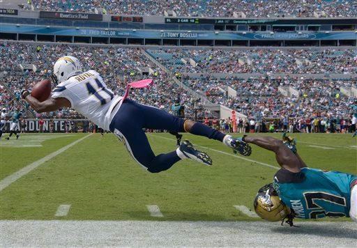 San Diego Chargers wide receiver Eddie Royal (11) catches a 27-yard pass for a touchdown as Jacksonville Jaguars strong safety Johnathan Cyprien, lower right, can't stop him during the first half of an NFL football game in Jacksonville, Fla.