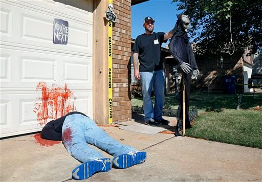 Johnnie Mullins poses with his controversial Halloween display featuring headless dummies dressed in his work clothes at his home.