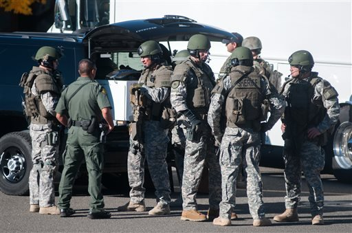 Swat team members secure the scene near Sparks Middle School in Sparks, Nev., after a shooting there on Monday, Oct. 21, 2013. Authorities are reporting that two people were killed and two wounded at the Nevada middle school. (AP Photo/Kevin Clifford)