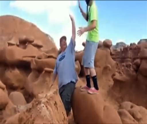 This frame grab from a video taken by Dave Hall shows two men cheering after a Boy Scouts leader knocked over an ancient Utah desert rock formation at Goblin Valley State Park.