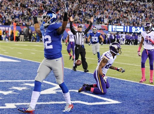 New York Giants wide receiver Rueben Randle (82) celebrates after catching a pass for a touchdown as Minnesota Vikings cornerback Chris Cook (20) and Mistral Raymond (41) react during the first half of an NFL football game Monday, Oct. 21, 2013.