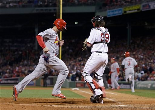 St. Louis Cardinals' Daniel Descalso scores past Boston Red Sox catcher Jarrod Saltalamacchia (39) on a hit by Carlos Beltran during the seventh inning of Game 2 of baseball's World Series Thursday, Oct. 24, 2013, in Boston.