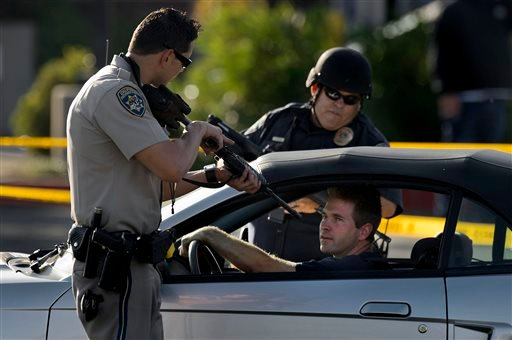 A California Highway Patrol officer and another emergency responder stop a vehicle at a checkpoint near the neighborhood where a federal immigration officer was shot and three local police officers were wounded during a violent confrontation.